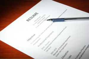 Closeup of resume with pen on wooden table