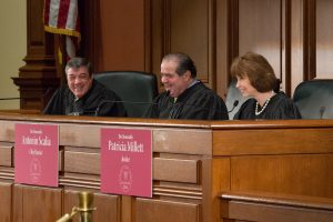 Antonin Scalia sits smiling at the bench with two other judges