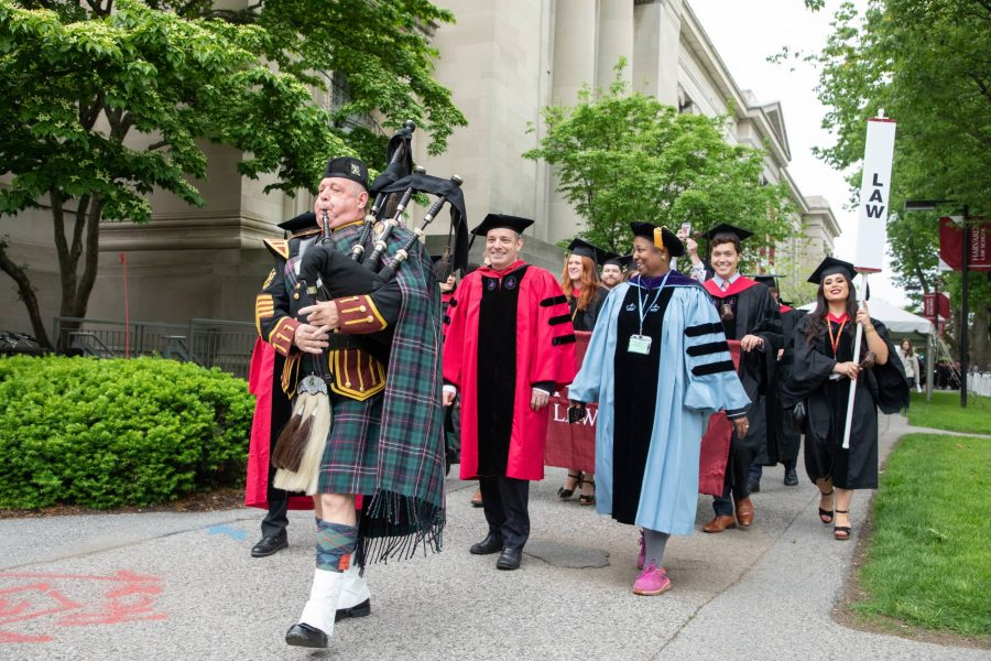 A bagpiper leads a procession of HLS faculty and students in regalia.