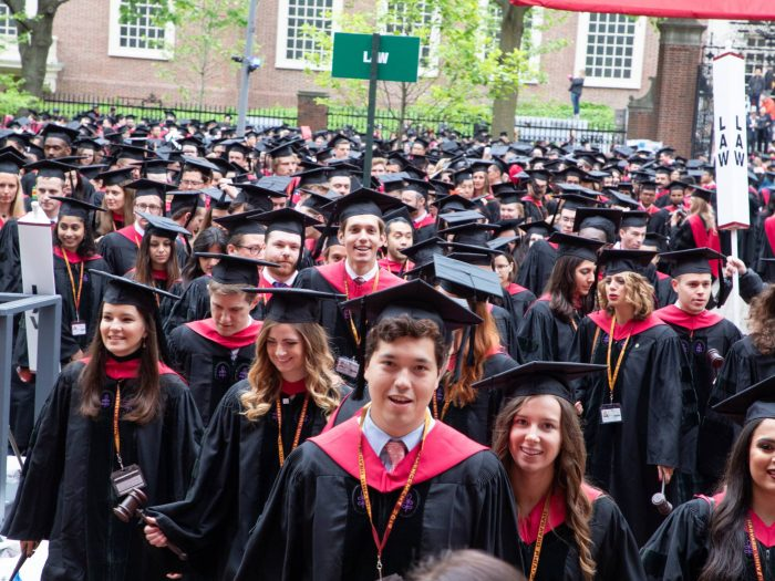 A crowd of graduates in caps and gowns process forward.