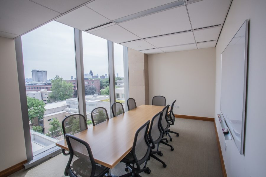 Interior boardroom with chairs and a table, view of Harvard buildings from window
