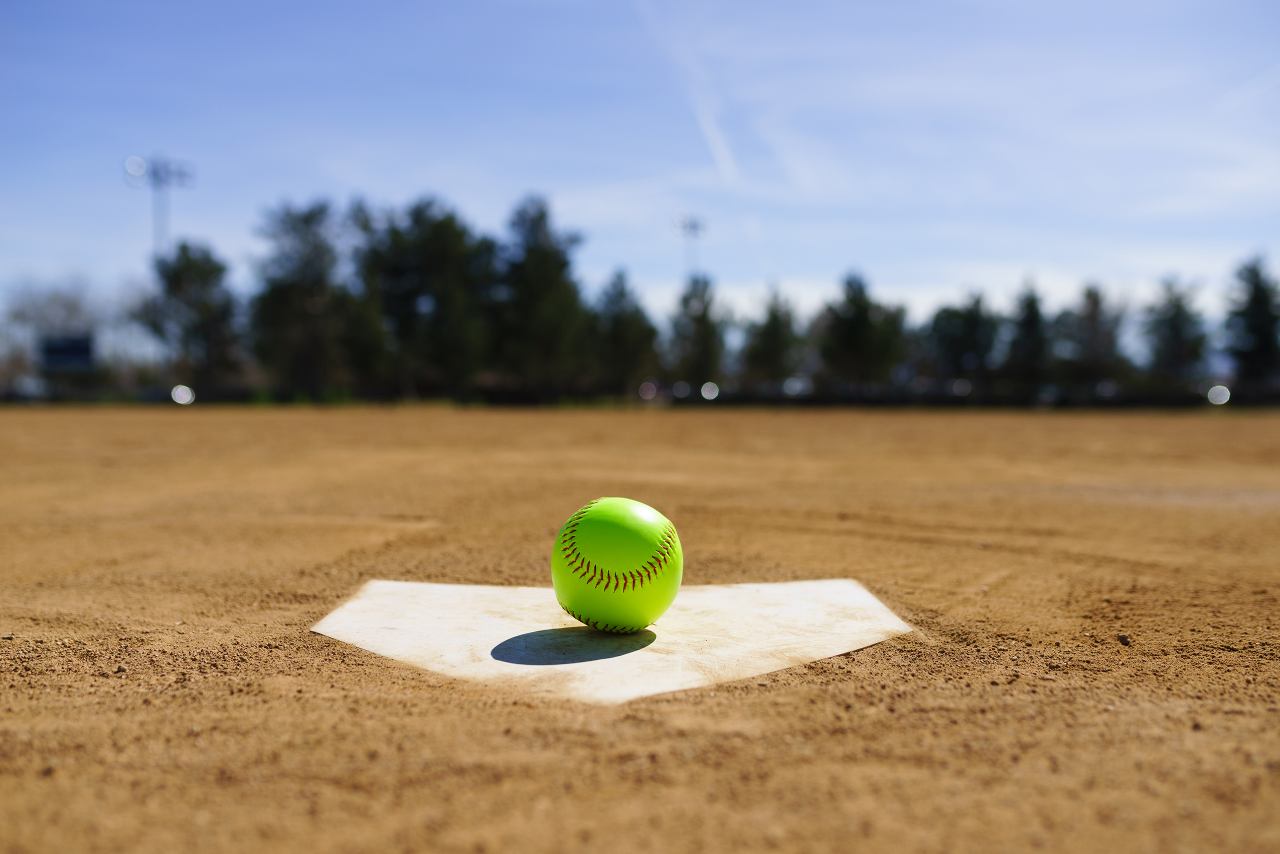 Softball rests on home plate in a field