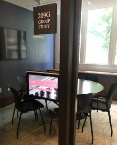 A new digital room sign outside of a freshly renovated Langdell Library Group Study Room with a table and chairs visible through the glass wall