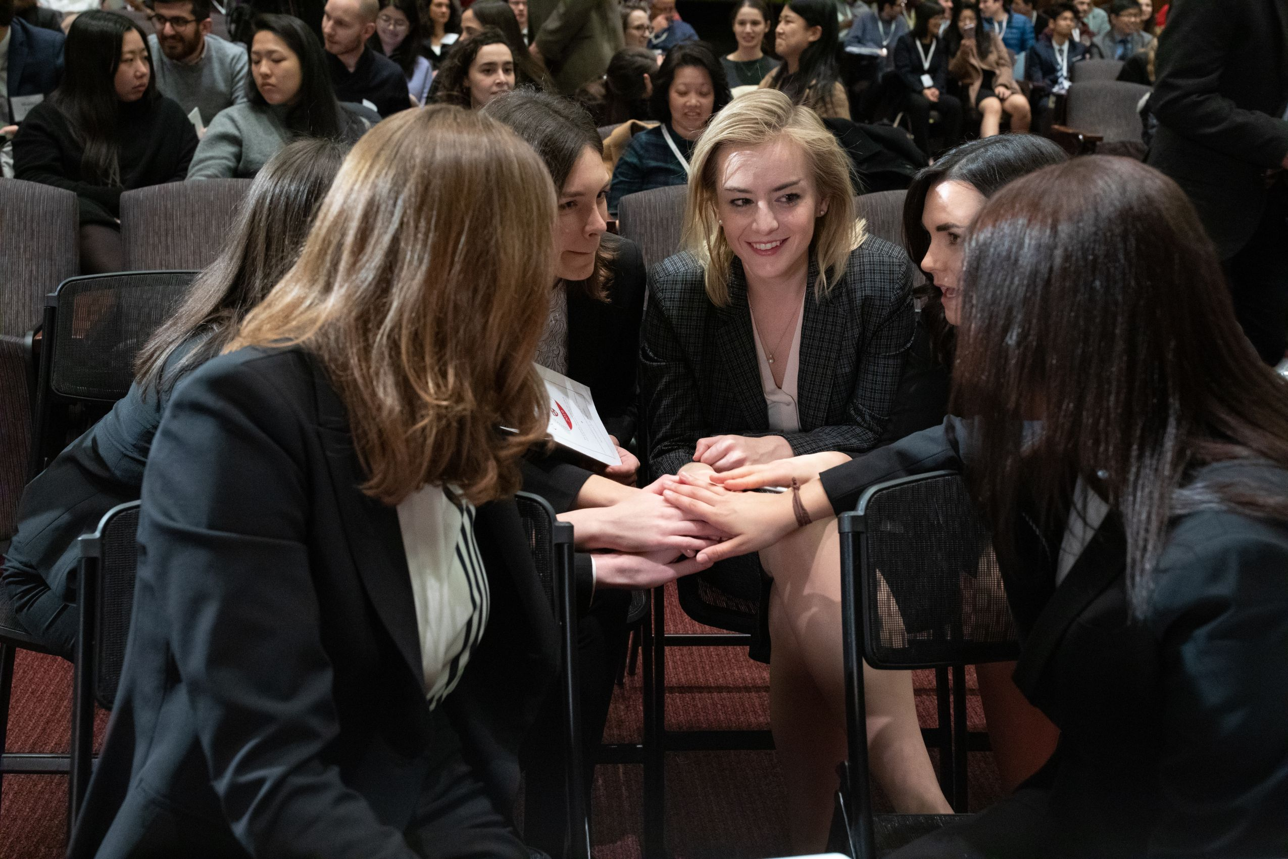 Finalists place their hands together at the Ames Moot Court Final Round.