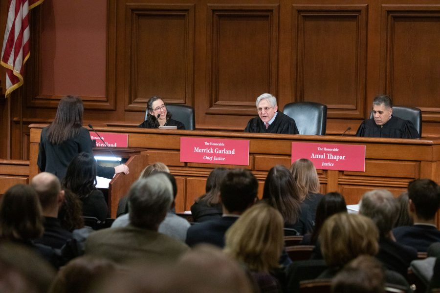 Hon. Merrick Garland speaks to a finalist standing at the podium of the Ames Moot Court Final Round.