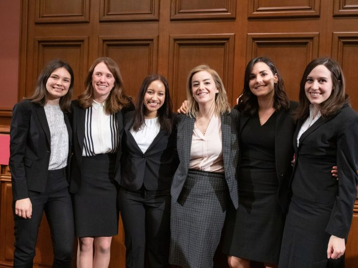 Six women participants in the Ames Moot Court final round stand together in the Ames courtroom.