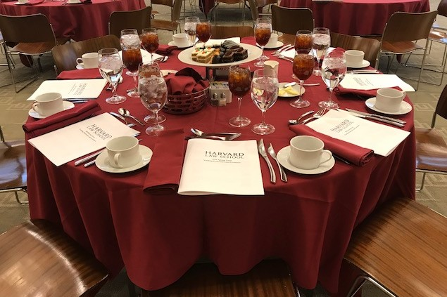 Interior shot of a banquet table featuring crimson linen and a dessert platter center piece