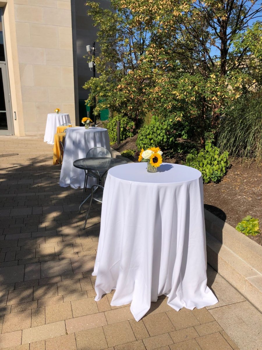 Exterior terrace with high tables covered in white linen with sunflower center pieces